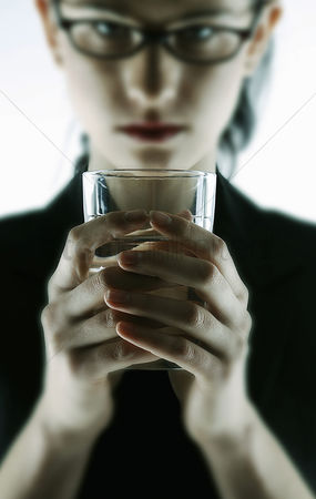 Bespectacled : Businesswoman holding a glass of water