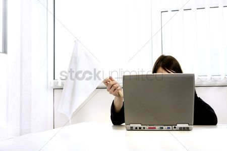 Flag : Businesswoman holding a white flag while using laptop