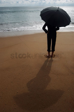 Relaxing : Businesswoman holding an umbrella on the beach