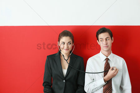 Contemplation : Businesswoman listening to businessman s heartbeat through a stethoscope