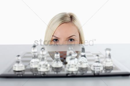 British ethnicity : Businesswoman peeking from under the table  chess set on the table