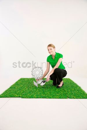 Cardboard cutout : Businesswoman planting a sunflower