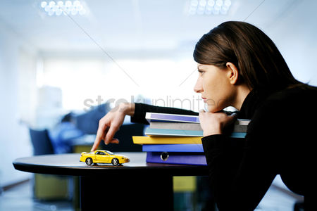 Thought : Businesswoman playing with toy car while thinking