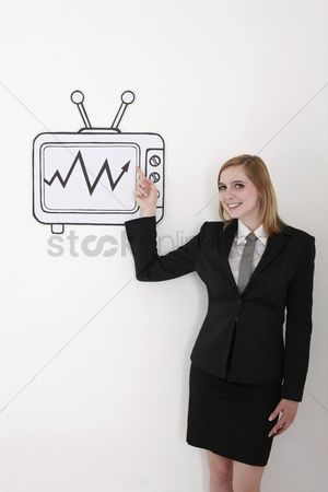 Cardboard cutout : Businesswoman pointing at stock market growth on television