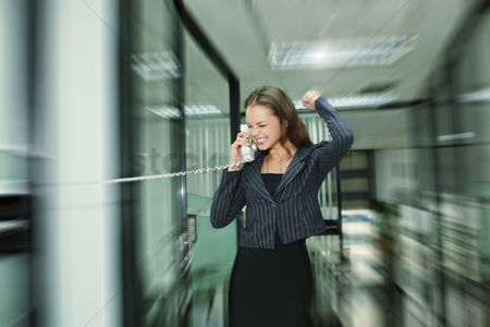 Smiling : Businesswoman punching the air while talking on the phone