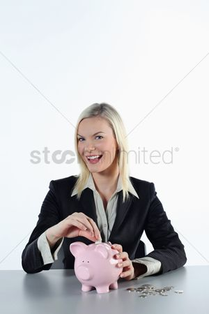 British ethnicity : Businesswoman putting coin into piggy bank