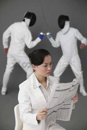 Fight : Businesswoman reading newspaper with two men fencing in the background