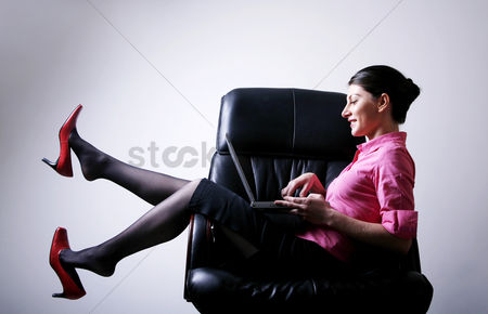 Notebook : Businesswoman sitting on the chair playing with laptop