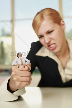 Forbidden : Businesswoman squeezing a tiny businessman