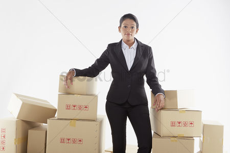 Malaysian indian : Businesswoman standing amongst a stack of cardboard boxes