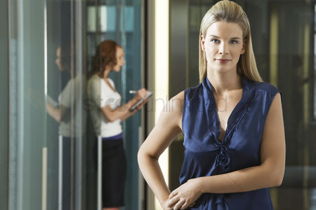 Interior background : Businesswoman standing in office corridor portrait