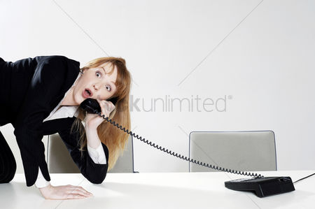 Answering calls : Businesswoman struggling to answer a phone call