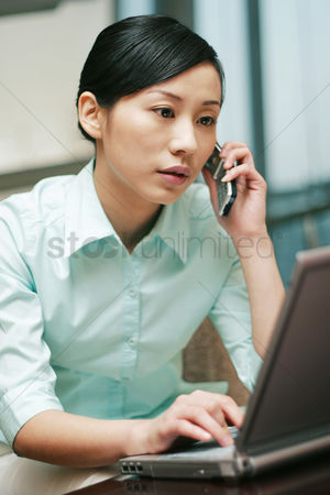 Cellular phone : Businesswoman talking on the hand phone while using laptop