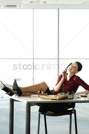 Attitude : Businesswoman talking on the phone with feet up on the table