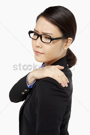 Frowning : Businesswoman touching her painful shoulder