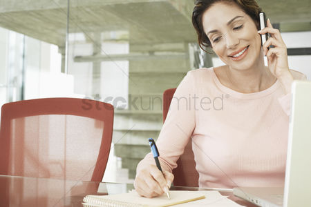 Pen : Businesswoman using mobile phone in office
