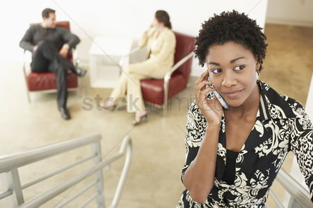Curly hair : Businesswoman using mobile phone on stairs
