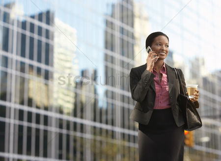 Cheerful : Businesswoman using mobile phone outside office building