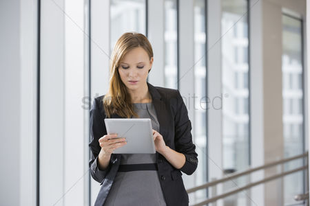 Three quarter length : Businesswoman using tablet pc in office
