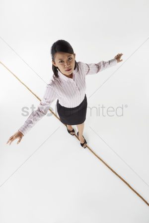 Rope : Businesswoman walking on a tightrope  worried