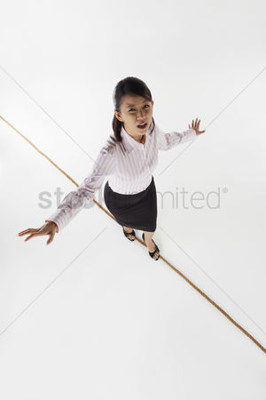 Careful : Businesswoman walking on a tightrope  worried