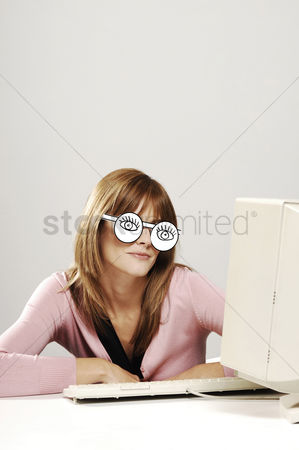 Cardboard cutout : Businesswoman wearing a cardboard cut-out spectacles while using computer desktop