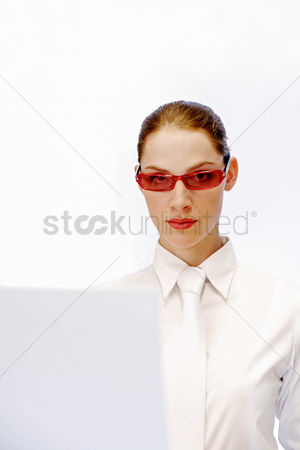 Corporation : Businesswoman wearing a funky red sunglass while using the laptop