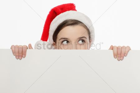 Contemplation : Businesswoman with santa hat peeking from behind a white board