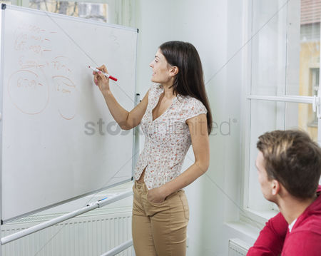 Czech republic : Businesswoman writing on whiteboard in meeting