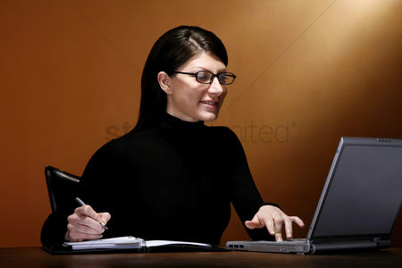 Notebook : Businesswoman writing while using laptop
