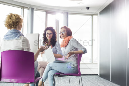Three quarter length : Businesswomen discussing in creative office