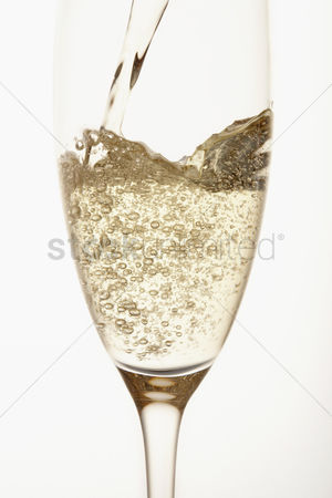 Food  beverage : Champagne being poured into glass close up in studio