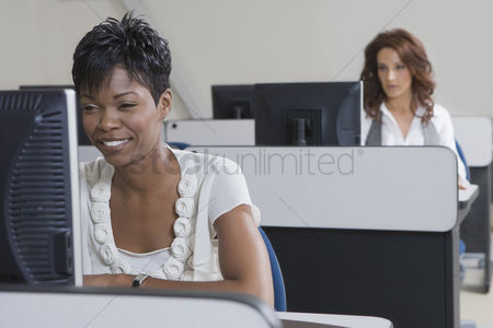 Interior background : Cheerful african american businesswoman working on computer