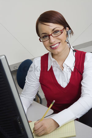 Notepad : Cheerful businesswoman sitting at desk