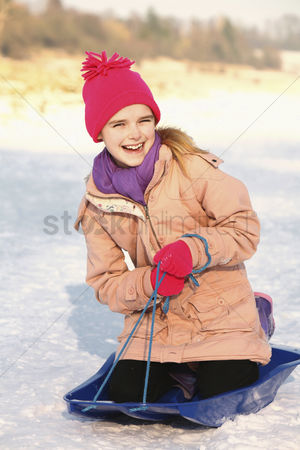 Gladness : Cheerful girl riding on sled