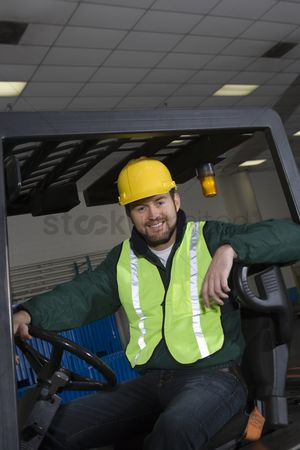 Interior : Cheerful man sitting on fork lift truck