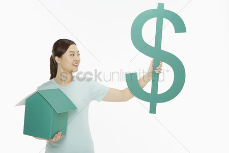 Dollar sign : Cheerful woman holding up a dollar sign and a cardboard house