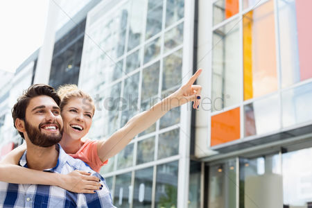 Arm raised : Cheerful woman showing something to man while enjoying piggyback ride in city