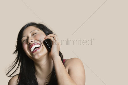 Smiling : Cheerful young woman talking on mobile phone over colored background