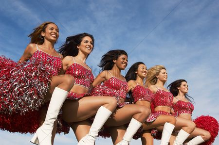Arm raised : Cheerleaders in a row kicking legs
