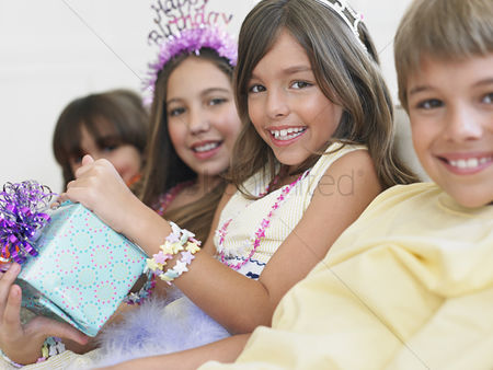 Birthday present : Children  7-12  sitting in row at birthday party one holding present