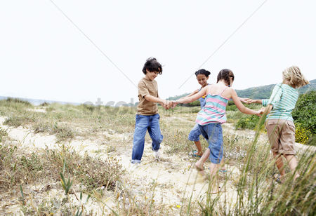 Pre teen : Children playing ring around the rosy on grassy beach