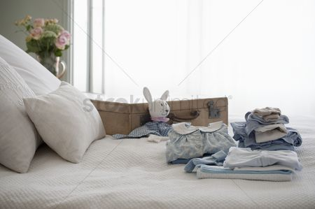 Loss : Childrens clothes folded on bed next to suitcase