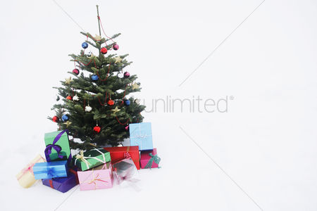 Remote : Christmas tree with presents in snow