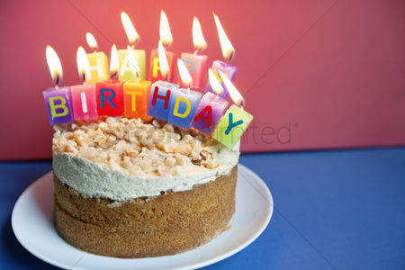 Celebration : Close-up of candles burning on birthday cake over colored background