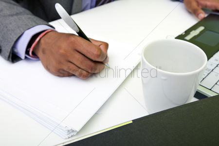 Furniture : Close up of indian mans hands writing on paper