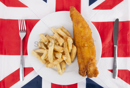 Flag : Close-up of junk food with fork and table knife over british flag