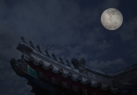 Moody : Close-up of ornate roof tiles on chinese building with moon background  night
