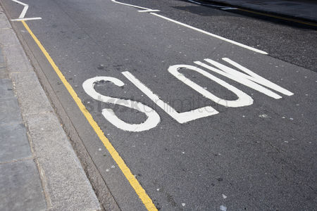 Transportation : Close-up of road marking saying slow in london uk