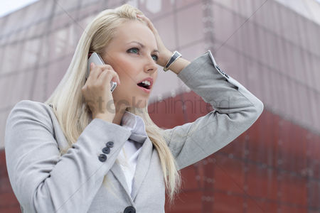 Cell phone : Close-up of shocked businesswoman communicating on cell phone against office building